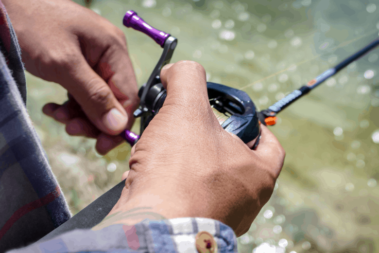 A mans hand holding a fishing reel