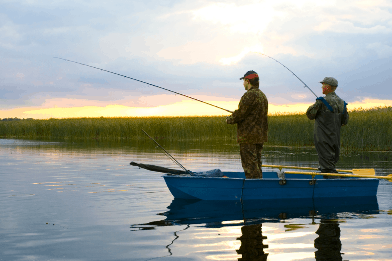 Two fishermen fishing from a boat