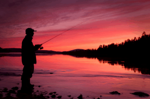 Man casting a reel at night