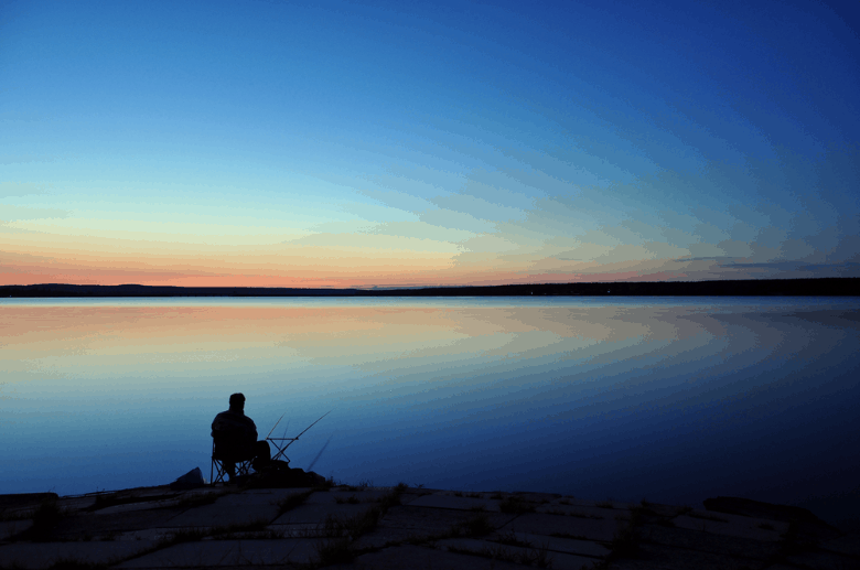 Fishing at night on the lake using a spinning reel
