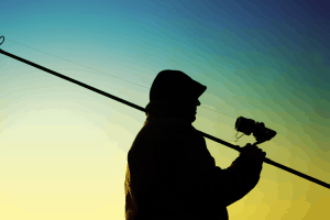 Fisherman with a fishing rod and spin reel in his hands