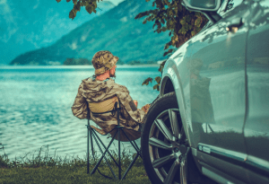 Man sitting down and fishing next to his car