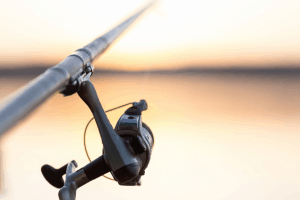 Image of someone fishing at sunset. Close-up fisherman hand with spinning reel