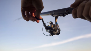 A mans hand holding a spinning fishing reel