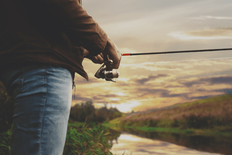 Young fisherman is fishing in river with spinning reel