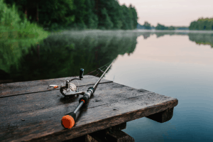 Fishing rod, spinning reel on the background pier river bank. Sunrise. Fog against the backdrop of lake. Misty morning. wild nature. The concept of rural getaway. Article about fishing day. Fishing Rod Spinning Reel Background Pier River Bank