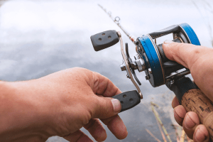 Man is fishing with a backcasting reel