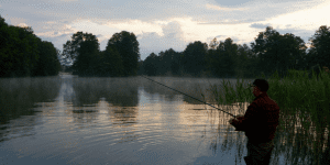 Silhouette of a fisherman standing by the lake and catching the fish